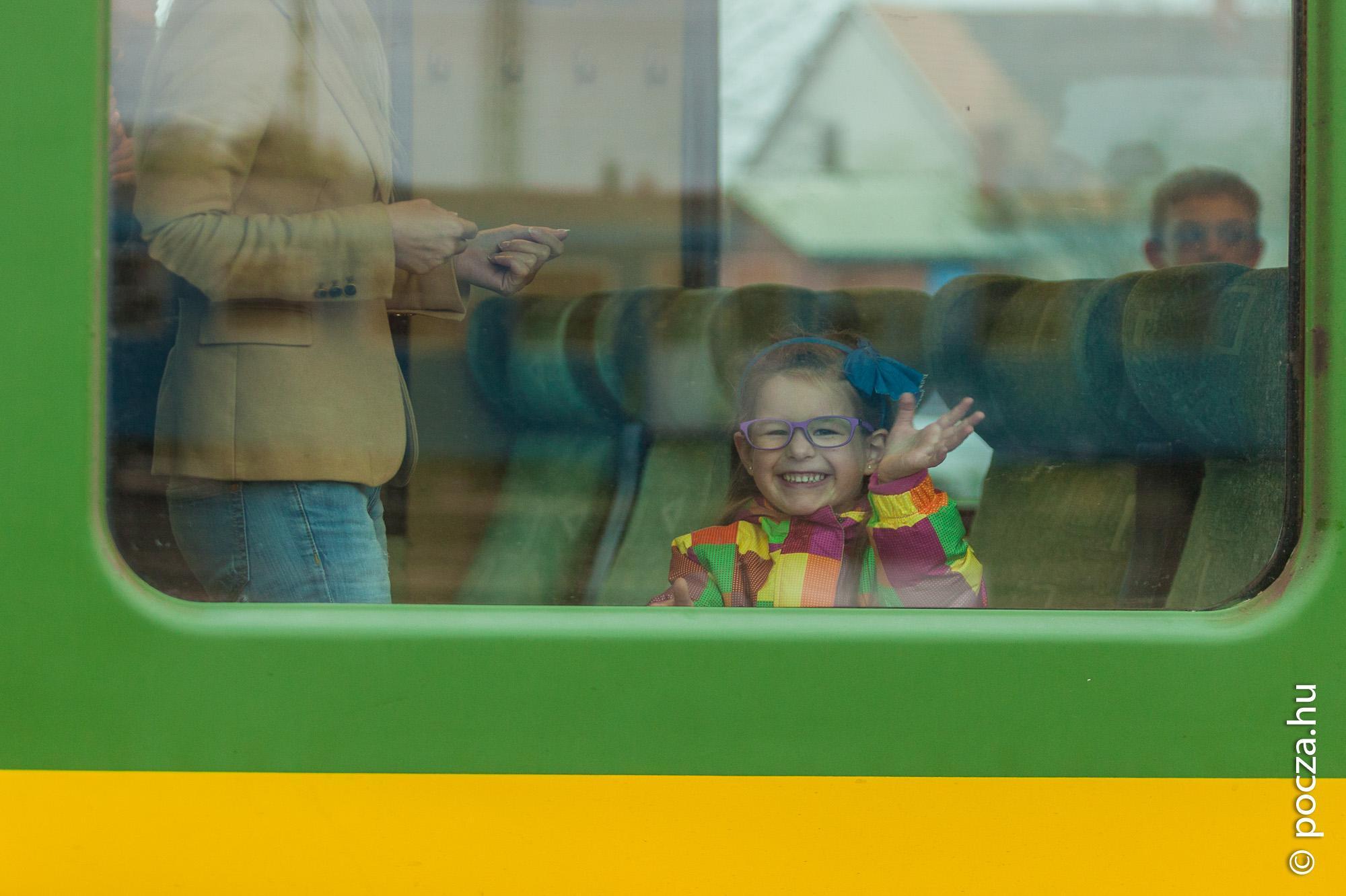 Kislány integet a vonat ablakon át